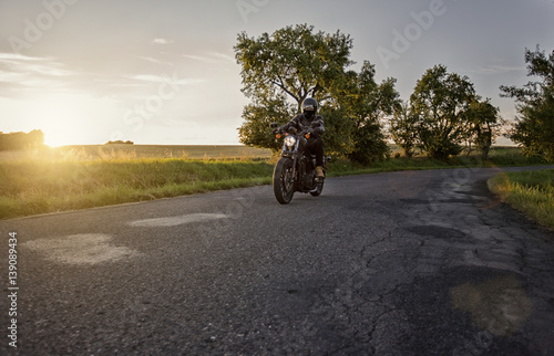 Foto  Chopper rider, biker, driving on a road during beautiful sunset