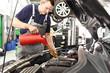 Kundendienst Ölwechsel am KFZ - Mechaniker in einer Autowerkstatt // Customer service Oil change