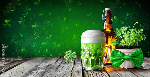 Láminas  St Patrick's Day - Green Beer In Glass With Bottle And Clovers On Wooden Table