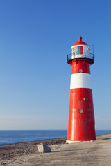 Fototapeta Marynistyczny Red and white lighthouse and a clear blue sky