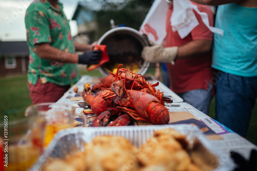 People preparing a large lobster boil outdoors Canvas Print