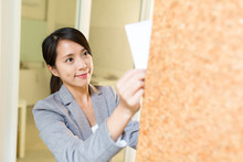 Business Woman Post Paper On Notice Board