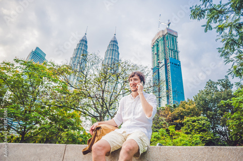 Foto op Aluminium Kuala Lumpur Young Man on the phone. Dressing in a white shirt, beige shorts. Young handsome businessman in casual clothes is sitting outside a business district. Mobile Office concept