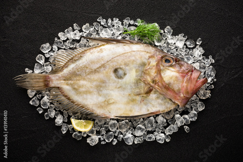 Fresh St Peter's fish on ice on a black stone background Wallpaper Mural
