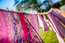 Holidays And Vacation On Countryside At Camping. Just Washed, Fresh And Aromatic Cotton Bed Sheets And Linen, Hang Out On A Laundry Line Outside In The Garden On A Sunny Summer Day. A Rural Scene.