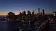 dusk descending shot of downtown NYC skyline revealing Brooklyn Bridge in foreground