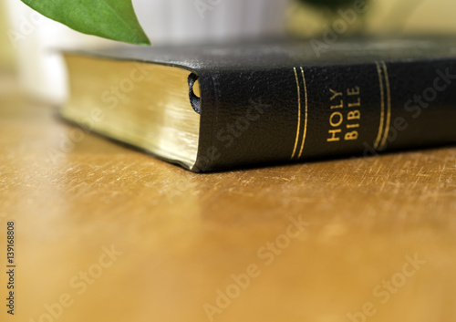 Holy bible lying on wooden table beside plant, golden glow background, Christian concept
