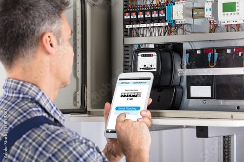 Fotografie, Obraz  Technician Doing Meter Reading Using Mobilephone