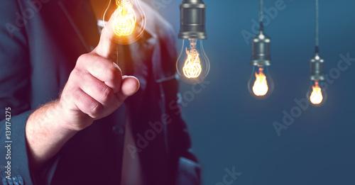 Fotografía Mann zeigt mit Finger auf eine Glühbirne