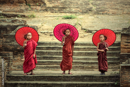 Myanmar The three novice walking on the Mingun pagoda and holding red umbrella in Mandalay,Myanmar Canvas Print