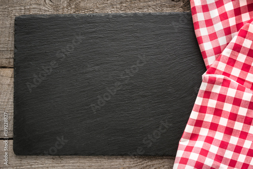 Rustic wooden boards, red checkered napkin and black slate dish with copy space for your menu or recipe Fototapete