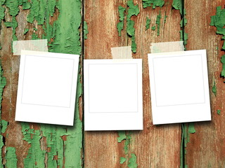 Three blank square photo frames on scratched wood