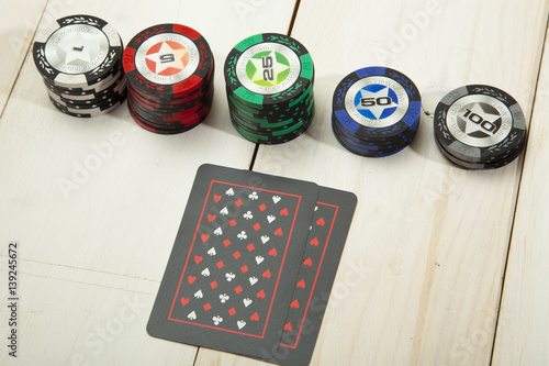 Game of poker chips and cards black on white wooden table плакат