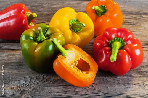 Foto Fresh colored bell pepper on wooden background