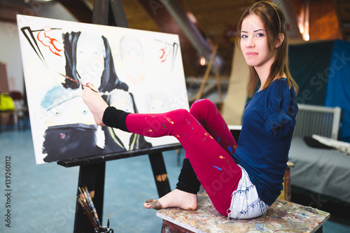 Disabled beautiful young artist painting incredible scenes in attic by holding paintbrush in her toes.
