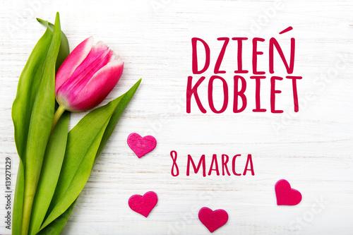 Women's day card with Polish words DZIEŃ KOBIET. Tulip flower small hearts on white wooden background. - fototapety na wymiar