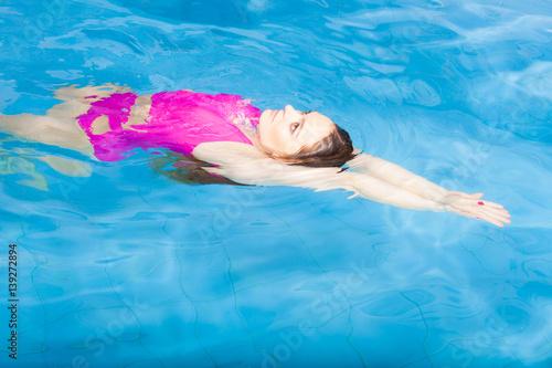 Foto op Aluminium Flamingo Beautiful woman swimming in pool