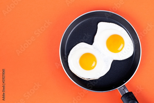 Deurstickers Gebakken Eieren fried eggs in a pan two eggs on an orange background