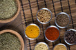 Various spices in bowls with fresh seasoning on rustic wooden background, closeup