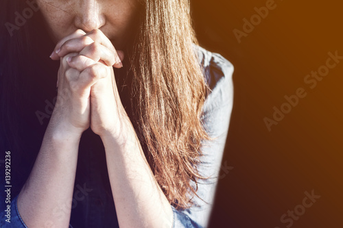 Fototapeta Woman praying in meadow at sunset