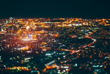 True Tilt Shift Shooting Of Business District In Night Metropolis From Very High Point: Square With Office Skyscrapers In Focus, Warm Lights From Windows, Strong Bokeh In Background And Foreground