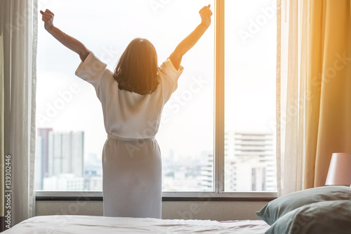 Easy lifestyle Asian woman waking up in the morning taking some rest relaxing in Poster
