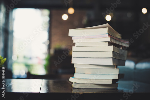 Fotografie, Obraz  piles of books on table over blurred library background.