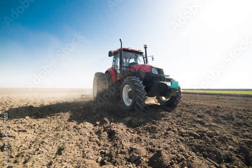 Fotografering  Tractor preparing land