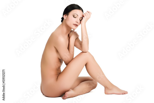 Young naked woman sitting on white background