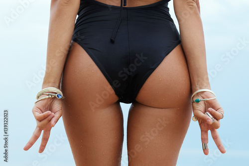 Fotografie, Obraz  Female buttocks and hands with victory or peace gesture