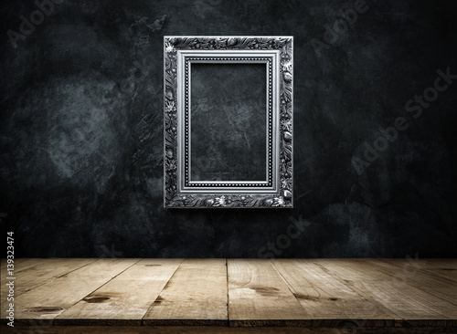 Fotografía  silver Antique picture Frame on dark grunge wall with Wooden table top, Empty ready for product display or montage