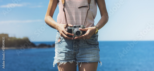 Fototapeta Tourist traveler photographer making pictures seascape on vintage photo camera on background yacht and boat piar, hipster girl enjoying peak mountain and nature holiday, ocean waves view obraz na płótnie