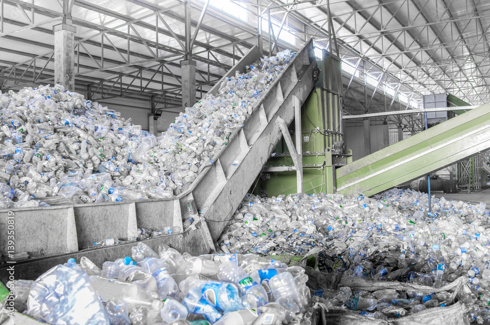 Fototapety, obrazy: closeup escalator with a pile of plastic bottles at the factory for processing and recycling. PET recycling plant