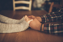 Couple In Love Holding Hands In A Cafe. Focus On Hands.
