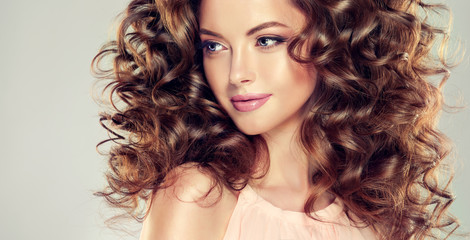 Beautiful model girl with  wavy  hairstyle  . Brunette woman with long  curly...