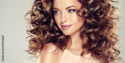 Foto op Plexiglas Kapsalon Beautiful model girl with wavy hairstyle . Brunette woman with long curly hair