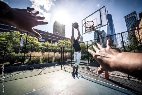 Foto  Two street basketball players playing hard on the court