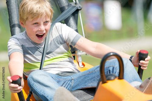 Poster Amusementspark Summer bobsled track. Happy boy having fun at amusement park