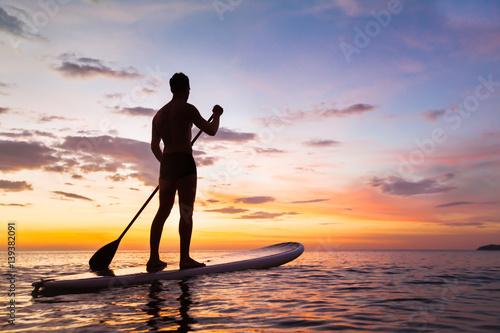 Plakat paddleboard na plaży o zachodzie słońca, wiosła stojących w Tajlandii