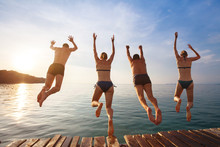Group Of Friends Jumping To The Sea From The Pier, Happy Beach Holidays