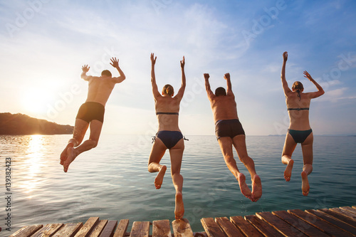 Foto  group of friends jumping to the sea from the pier, happy beach holidays