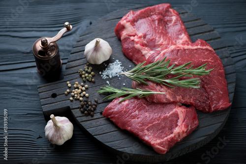 Photo  Black wooden chopping board with raw seasoned rump beefsteaks, studio shot