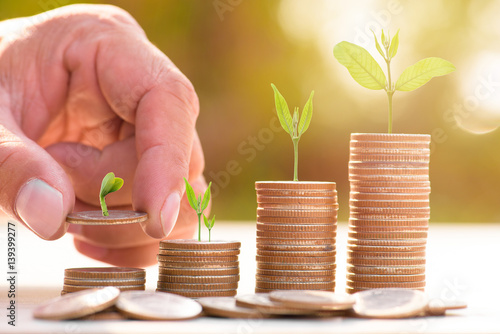 Fotografía Close up of male hand stacking gold coins with green bokeh background ,Business Finance and Money concept,Save money for prepare in the future