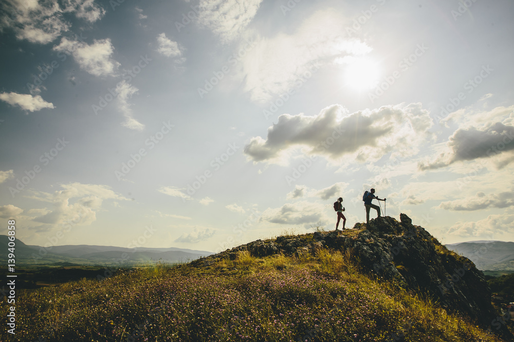 Fototapety, obrazy: Hikers with backpacks walking on top of a mountain and enjoy hiking