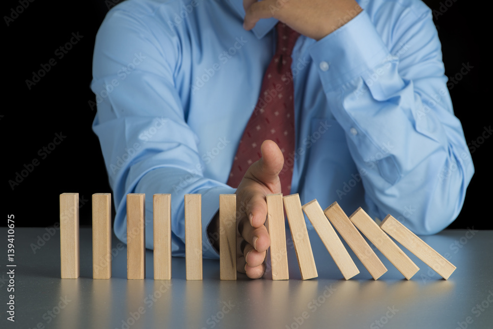 Fototapeta Close up view on hand of business woman stopping falling blocks on table for concept about taking responsibility.