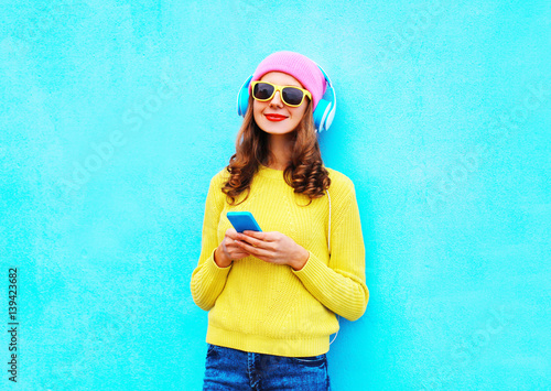 Cadres-photo bureau Magasin de musique Fashion carefree woman listening to music in headphones with smartphone wearing a colorful pink hat yellow sunglasses sweater over blue background