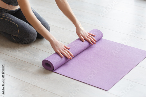 Obraz Young yoga Woman rolling her lilac mat - fototapety do salonu