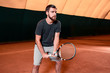 Handsome young man in t-shirt holding tennis racket on tennis court