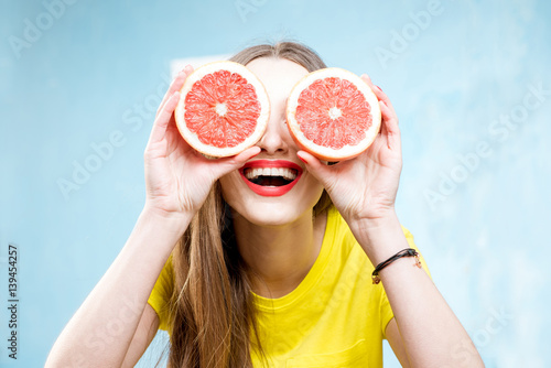 Fotografia  Colorful portrait of a beautiful woman grapefruit slices on the yellow backgroun