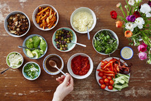 Variety Of Salads In Bowl Hand With Spoon Taking Brown Sauce